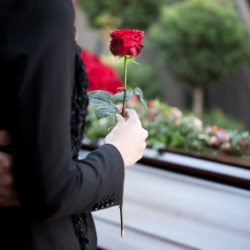 owned-image-woman-wiht-rose-at-casket